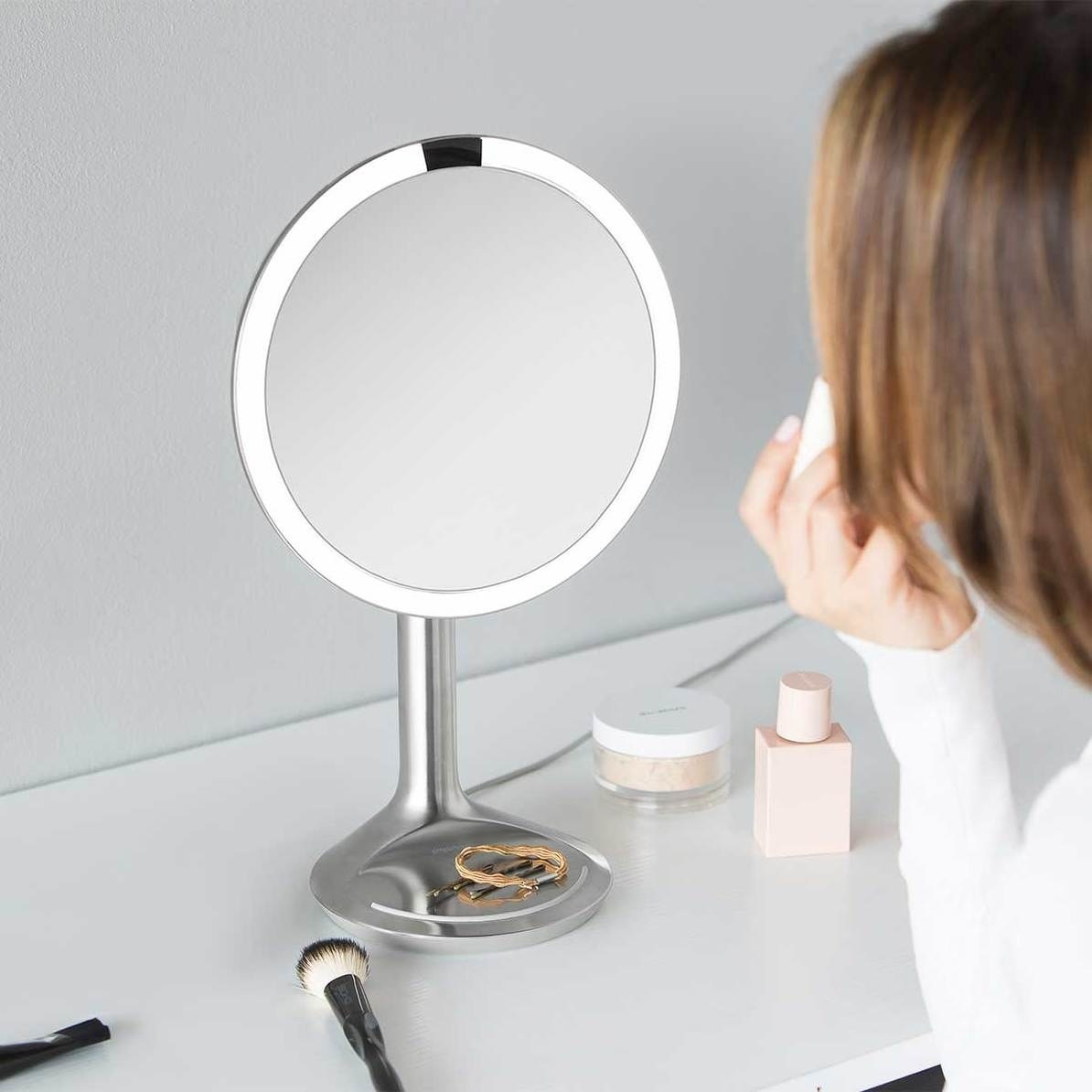 round mirror circled with LED on a stand with jewelry