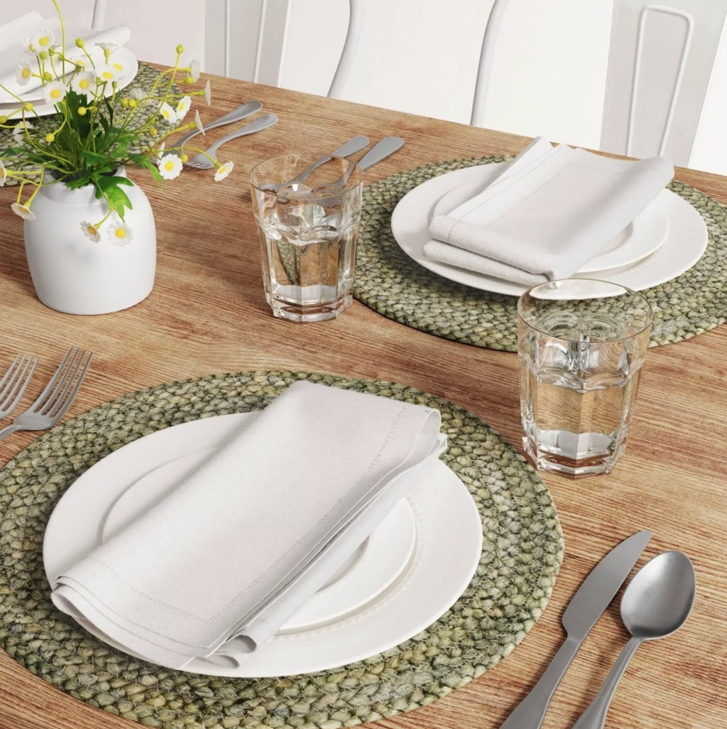 The placemats in grey underneath a fully set table