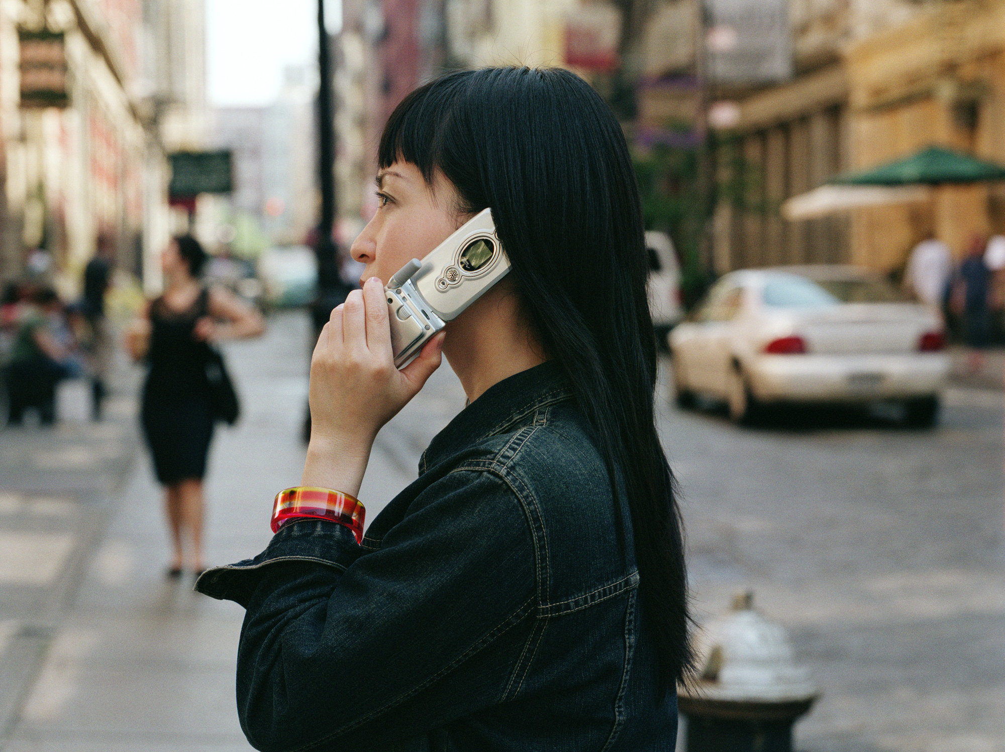 Someone talks on the phone using a flip cellphone