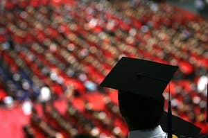 A college graduate in a  graduation cap looks out over a sea of fellow students