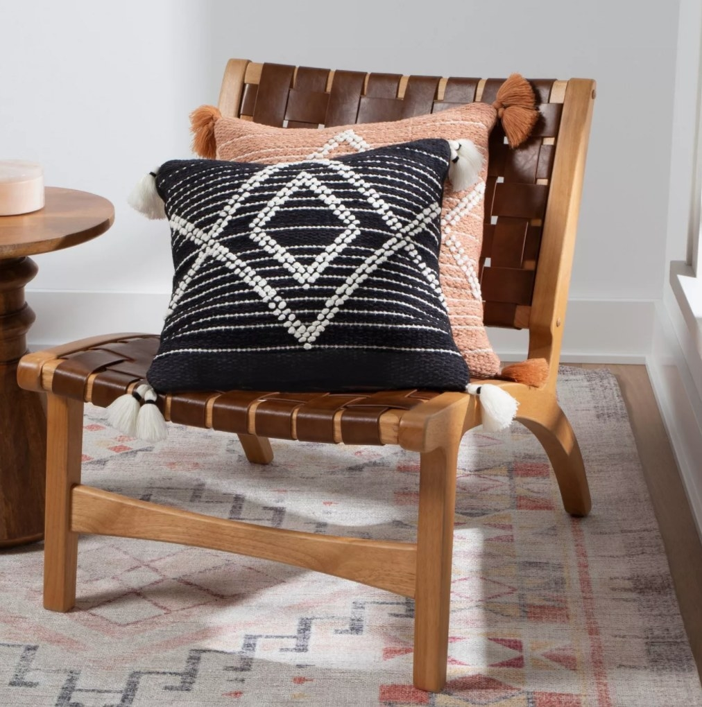 the pillows in black and orange on a woven leather chair