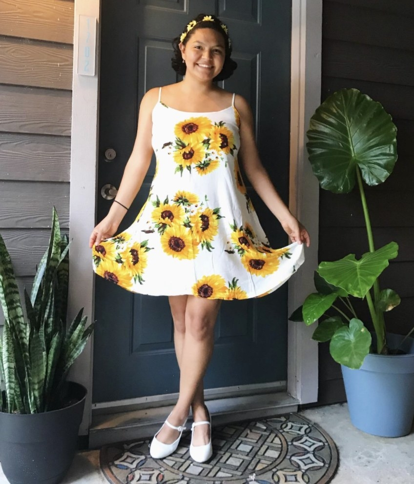 A person wearing a white dress with yellow sunflowers on it