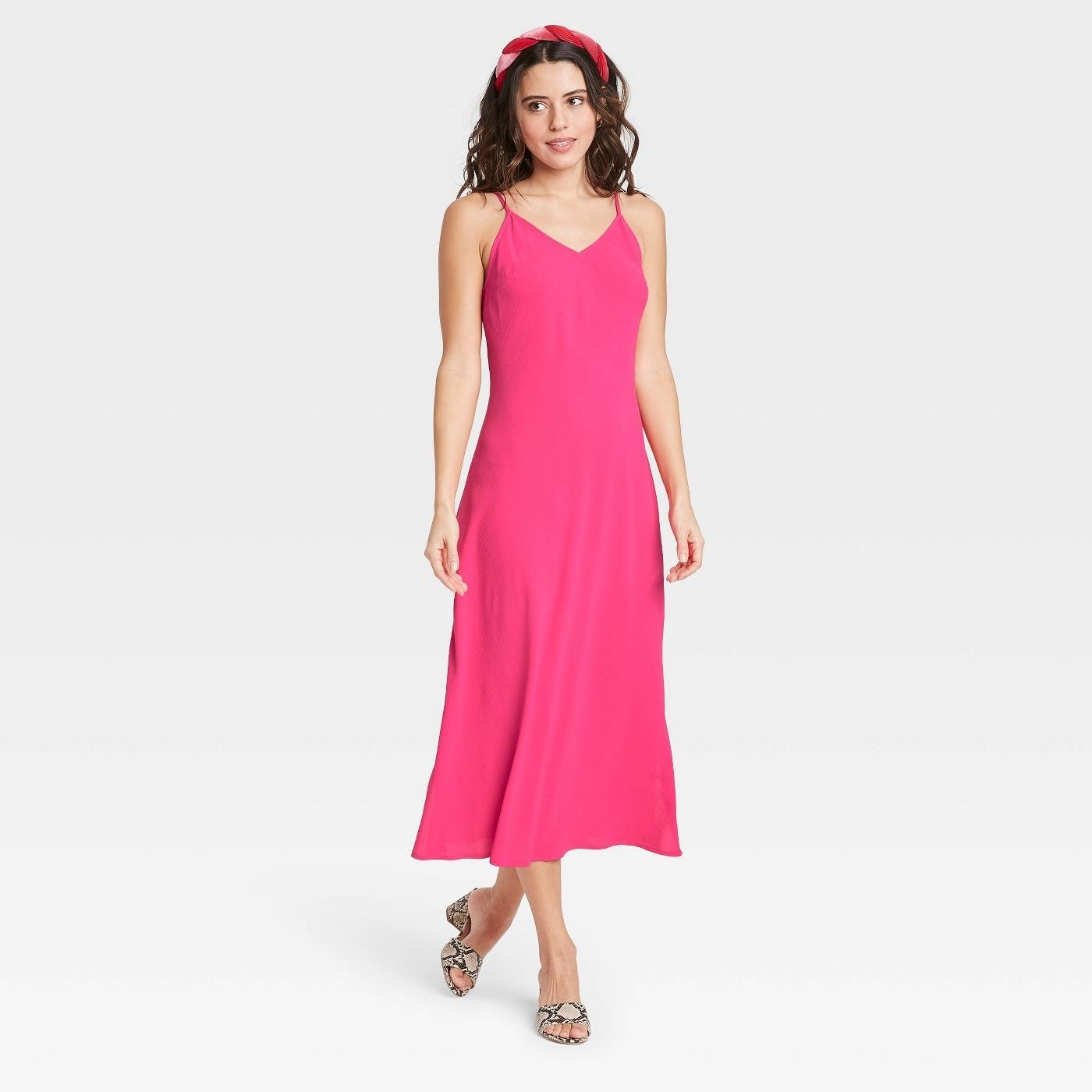 Model wearing pink dress that stop above the ankle