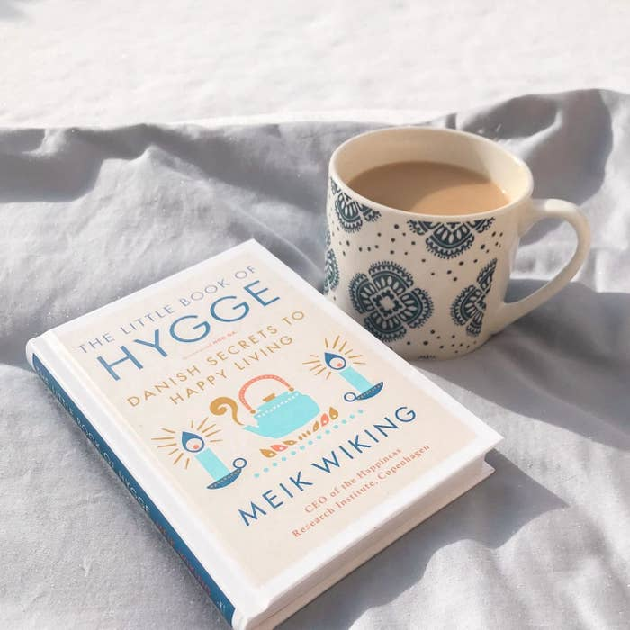 the book next to cup of tea on reviewer's bed