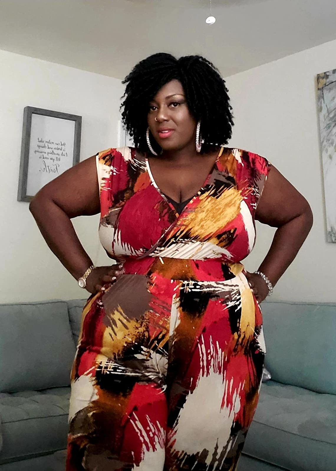 reviewer in red, gold, and white pattern v-neck jumpsuit
