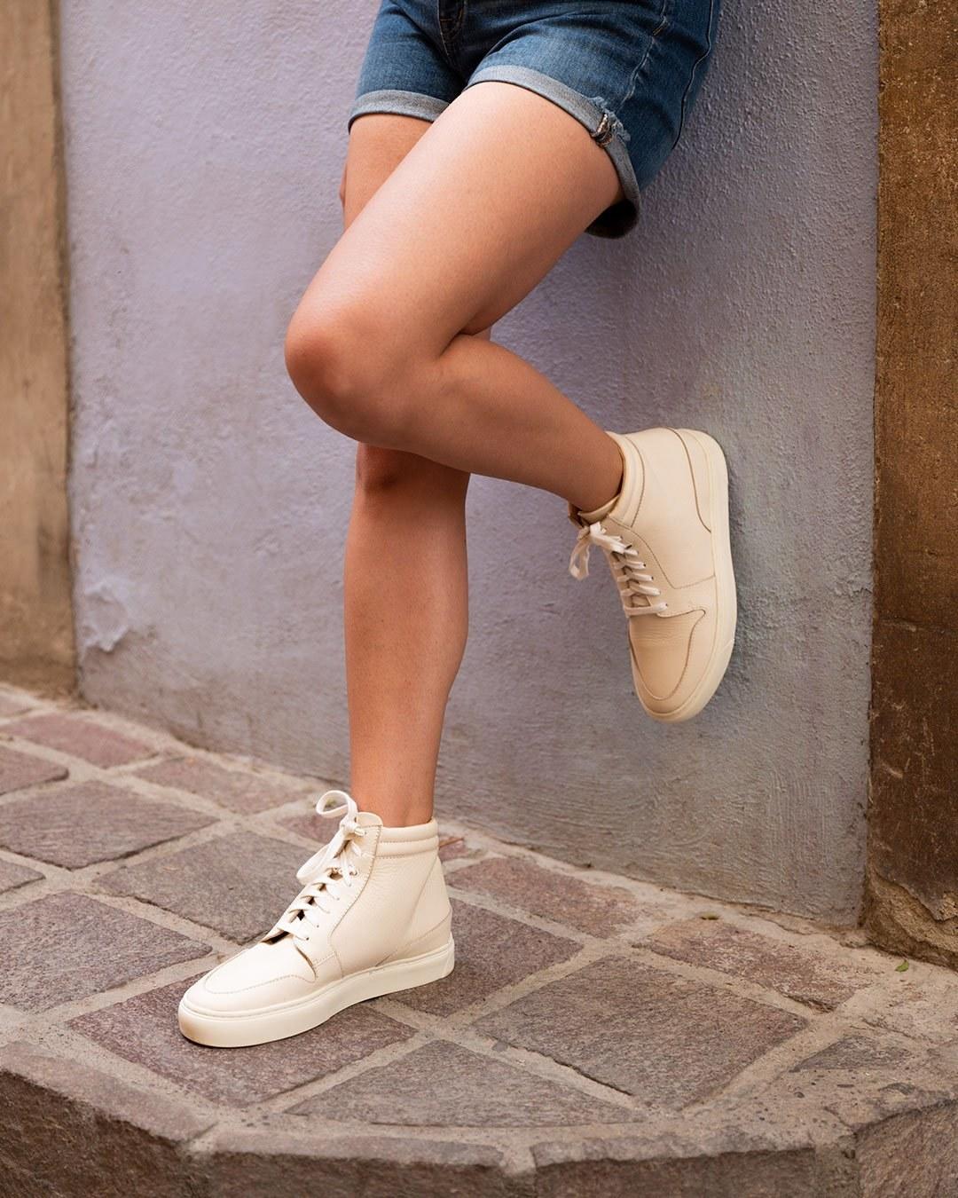 model wearing bone-colored high top sneakers