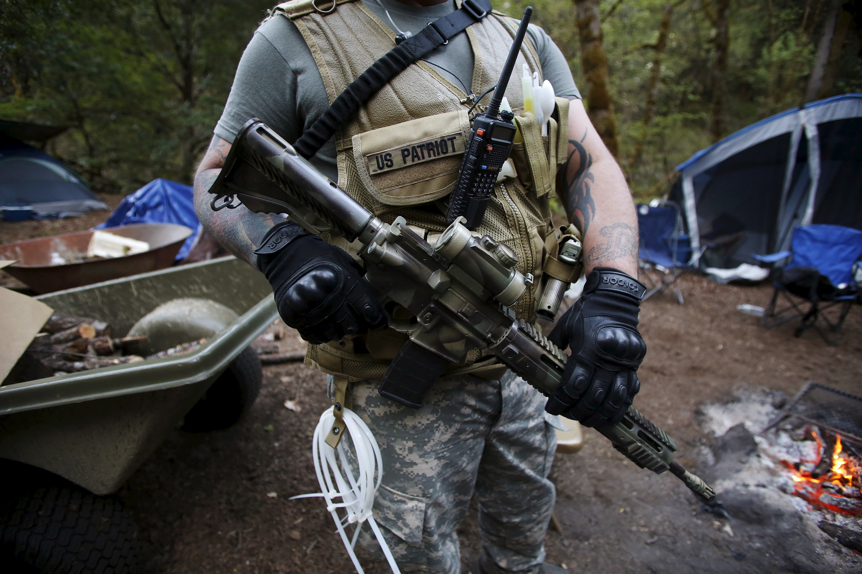 A man wearing tactical gear, carrying a gun, and with zip ties hanging from his vest