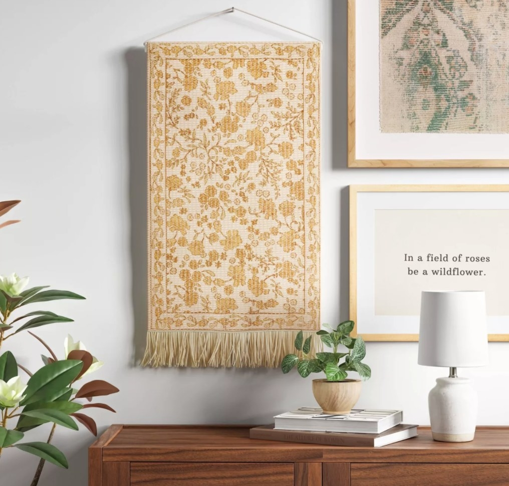 the yellow tapestry hanging above a cabinet next to two paintings