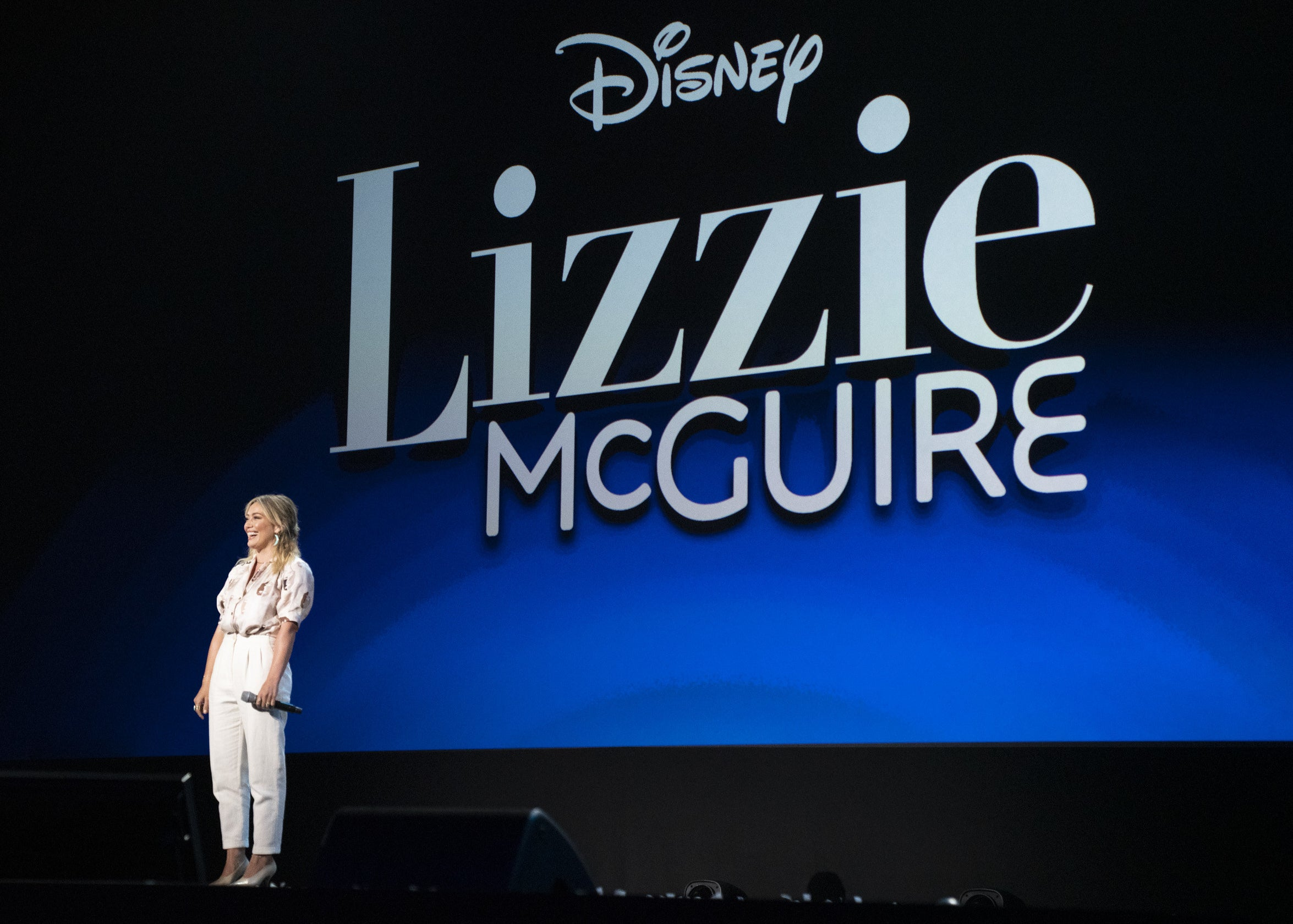 """Hilary stands on stage in front of the """"Lizzie McGuire"""" logo at a Disney event"""