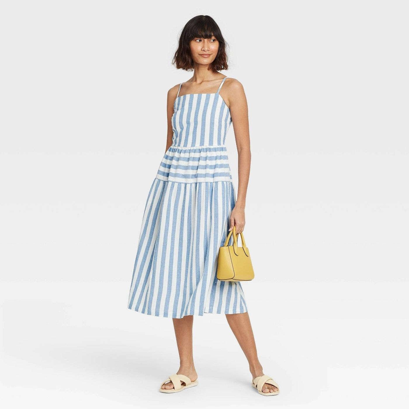 Model wearing a blue and white striped dress that goes past the ankle