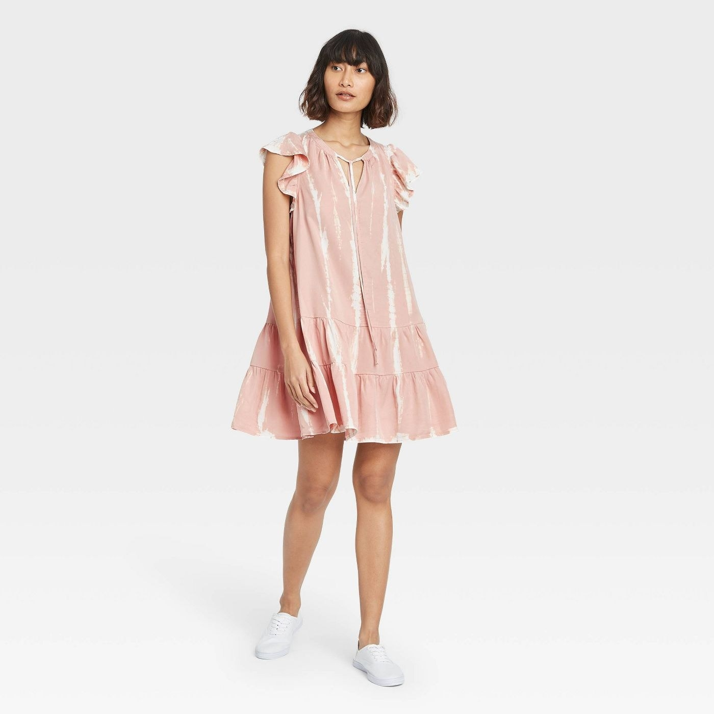 Model wearing baby pink dress that stop above the knee