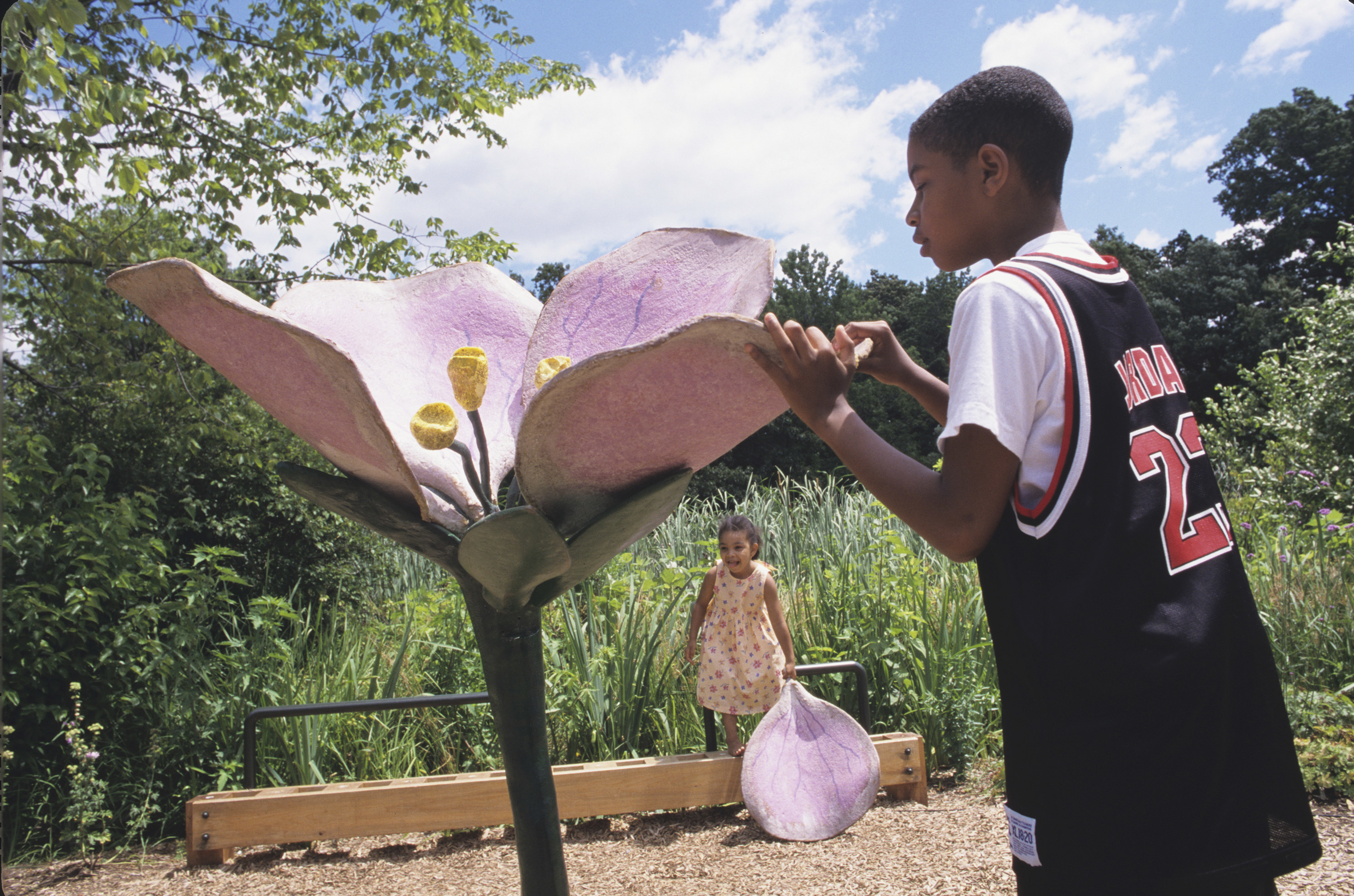 Two children play with novelty oversize flowers outside on a warm day