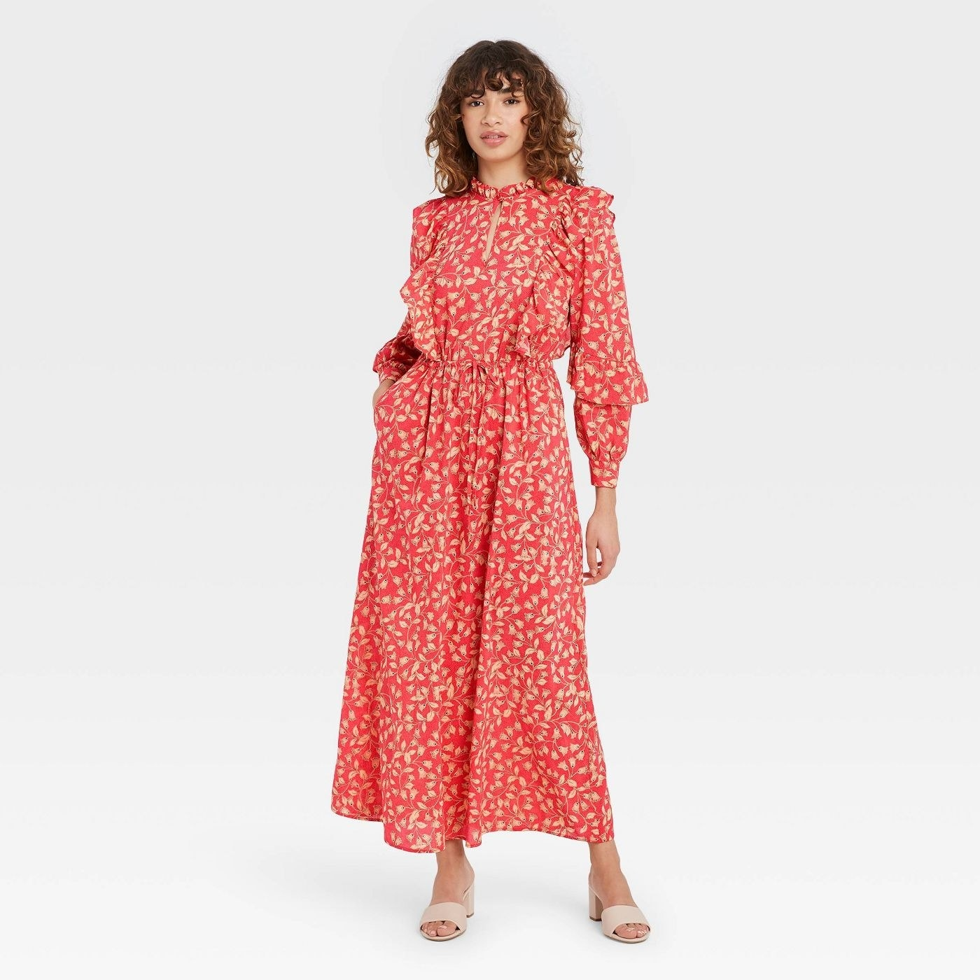 Model wearing red dress with beige floral print