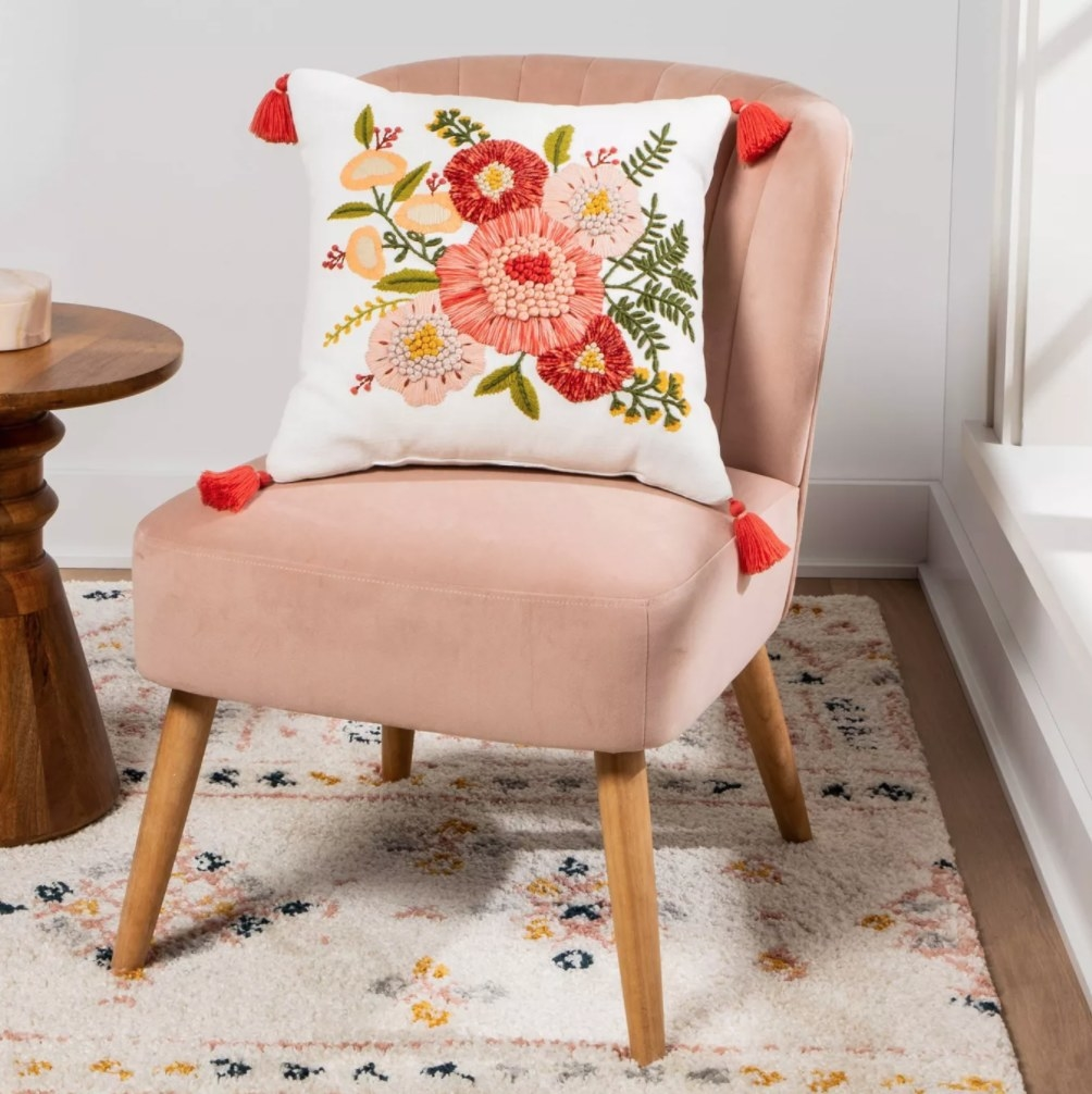 The pillow propped on a pink chair