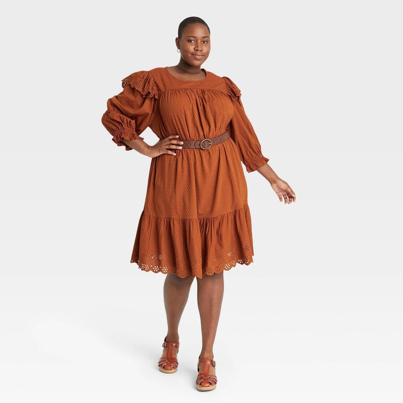 Model wearing burnt orange dress, stops at the knees