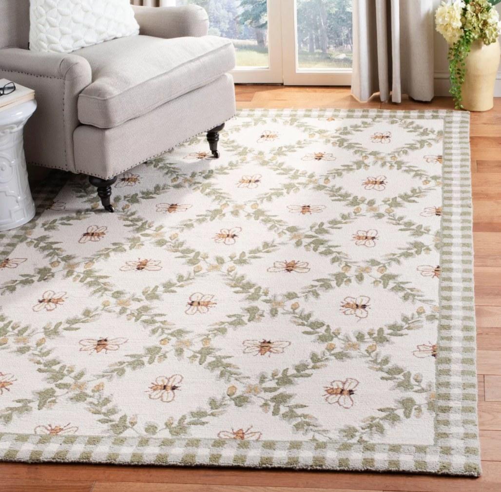 The rug on hardwood under a grey armchair