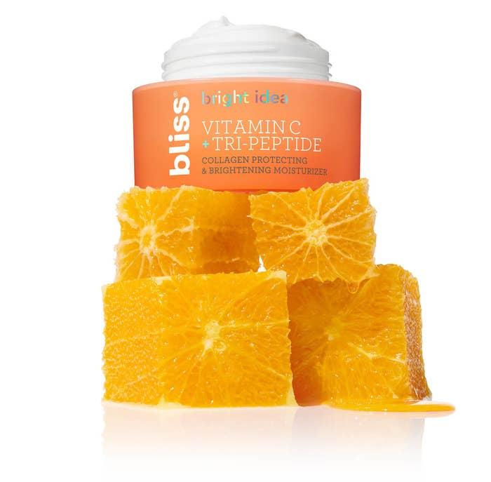 A jar of vitamin C cream on top of orange slices