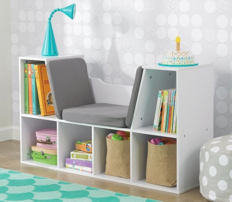 White bookcase with built-in gray padded bench