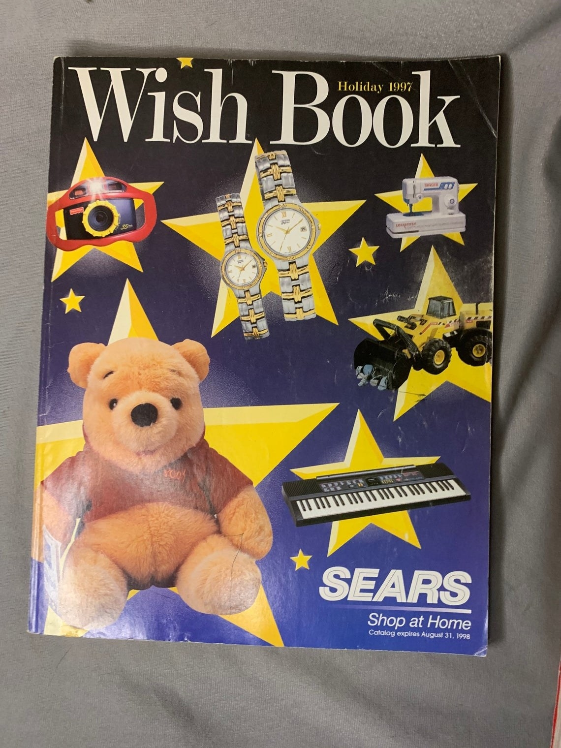 A holiday 1997 Wish Book with a Winnie the Pooh stuffed animal and various other items on the cover