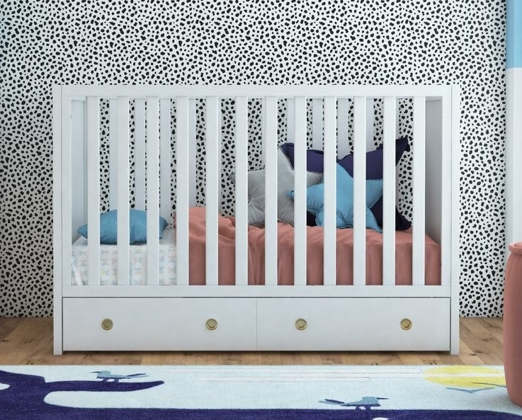 White convertible crib with storage drawer and gold hardware underneath