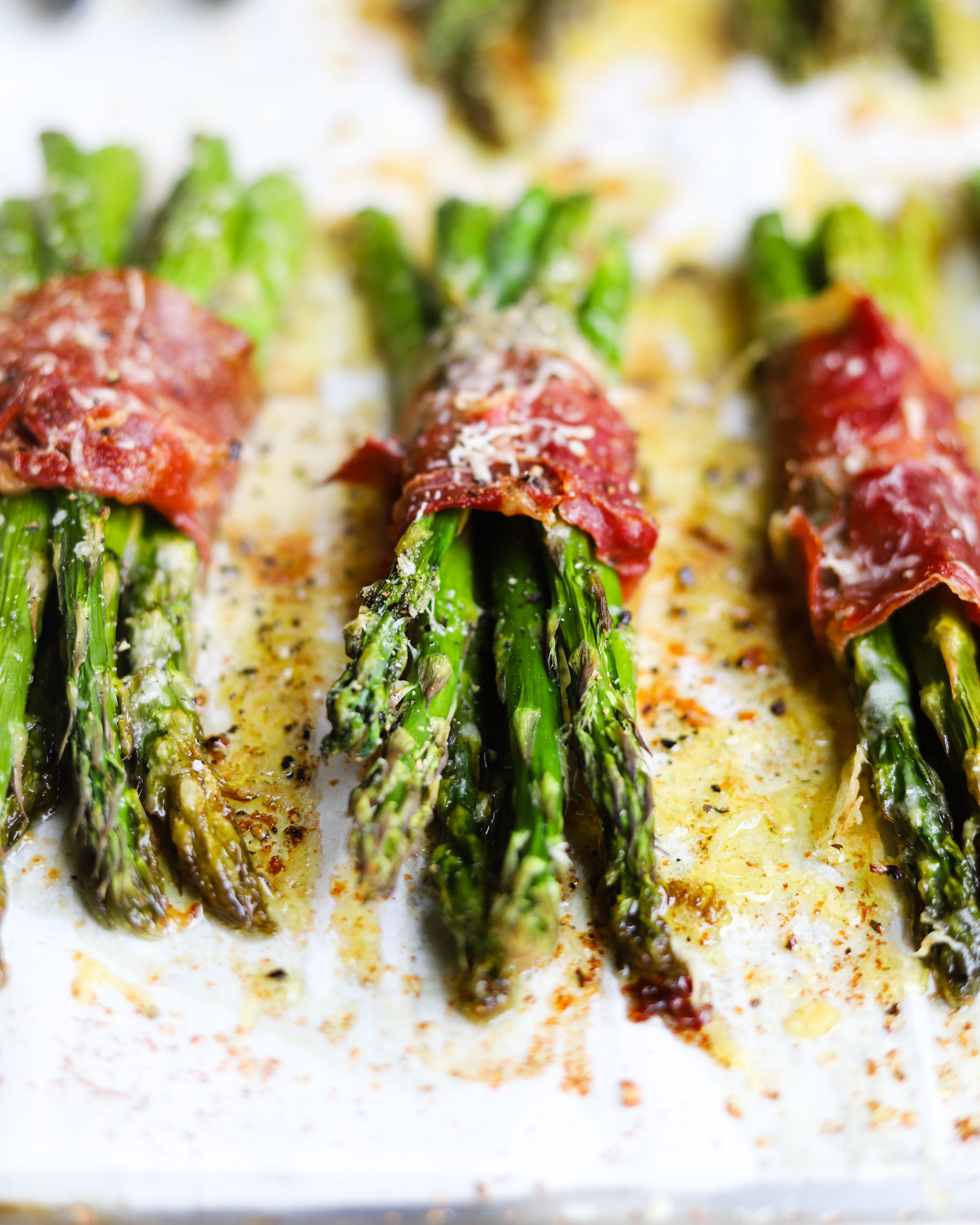 Bundles of cheesy roast asparagus wrapped in prosciutto.