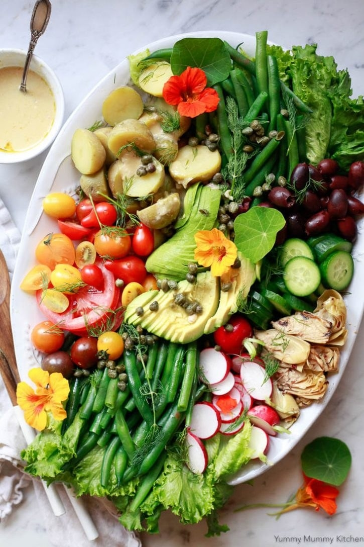 Niçoise salad with tomato, green beans, radish, cucumber, avocado, and more.