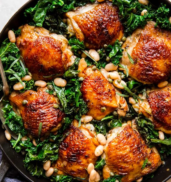 Skillet chicken thighs with kale and white beans.