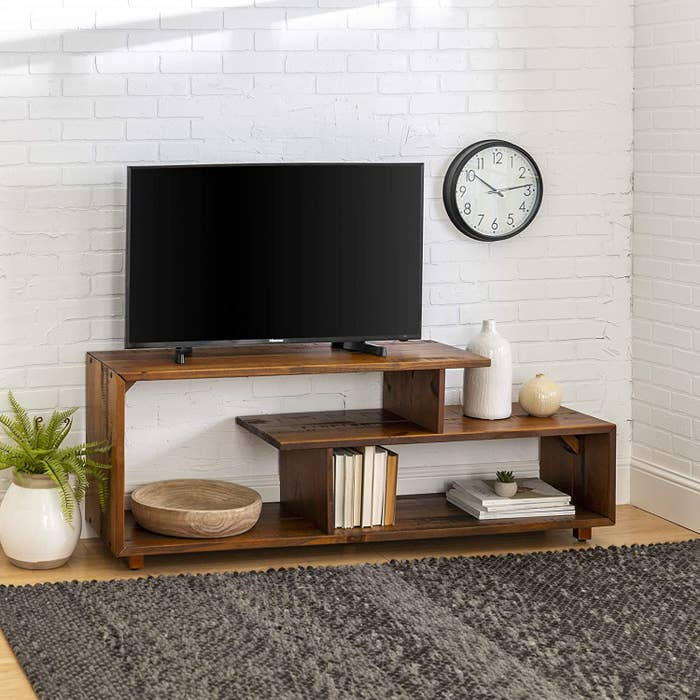 amber TV stand styled with books and other decor