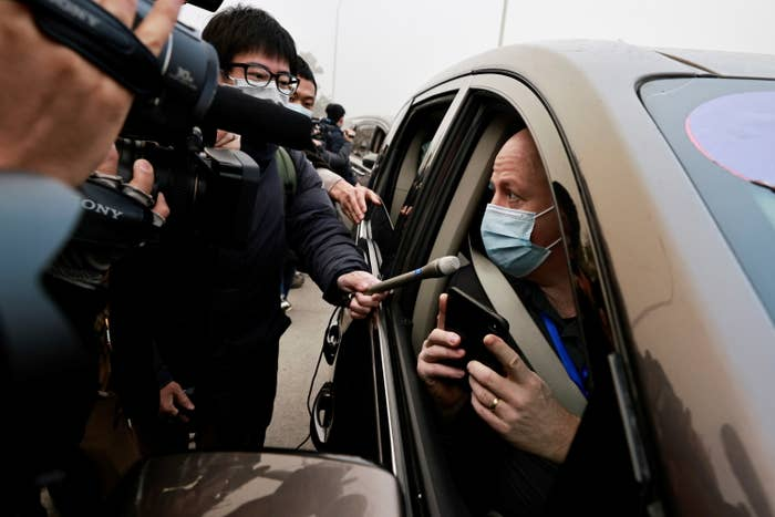 People with cameras and microphones surround a man wearing a face mask sitting in his car