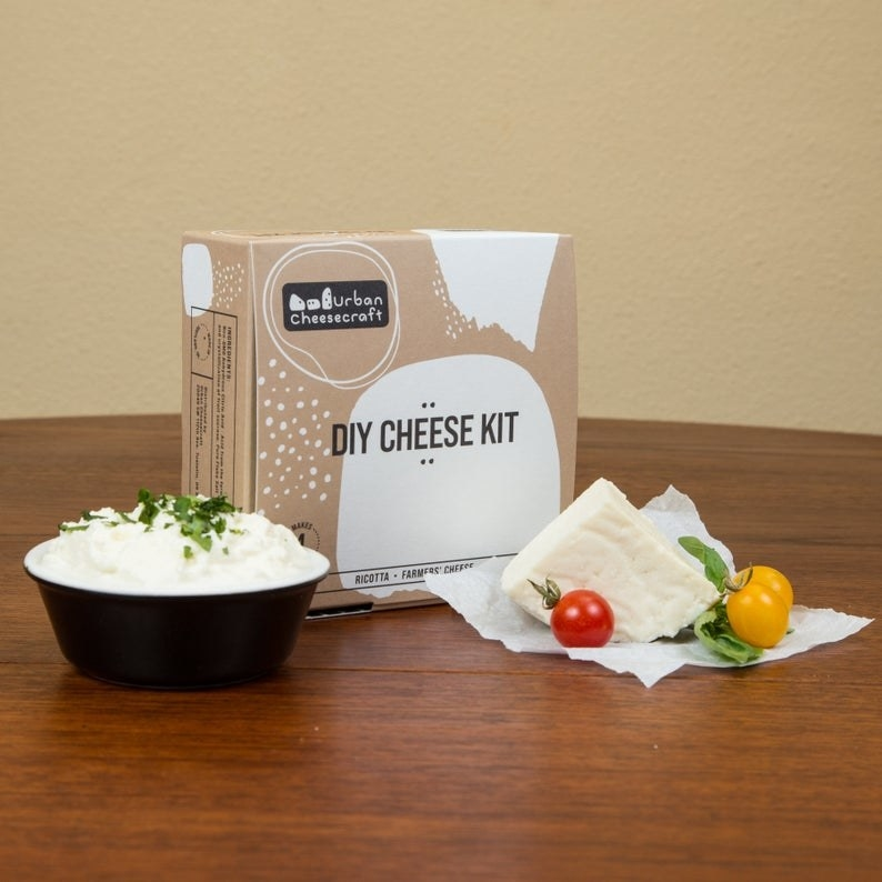 The DIY cheese set box with supplies and the cheese on a table