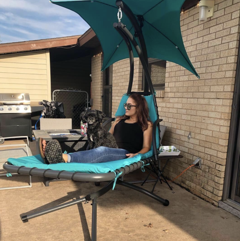 reviewer in chaise lounge chair suspended off the ground with an umbrella for shade