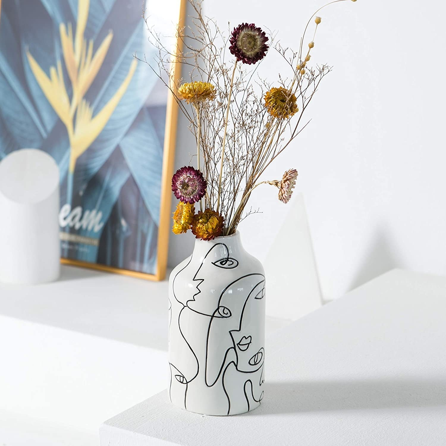 the white etched vase with a bouquet of dried flowers