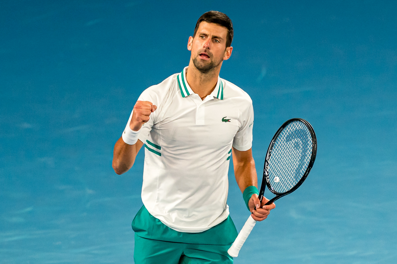 Novak Djokovic fist pumping on tennis court.