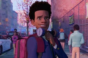 miles morales smiles with large headphones resting on his shoulders