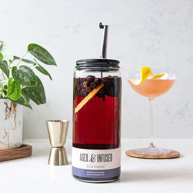 A transparent bottle with infused dried fruit and a straw