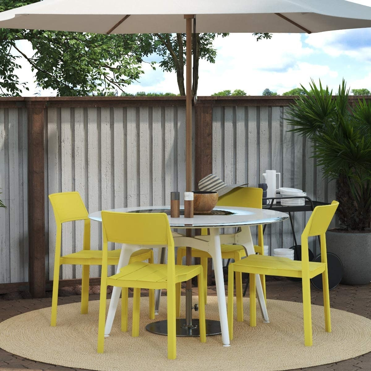outdoor round table with simple yellow chairs around it