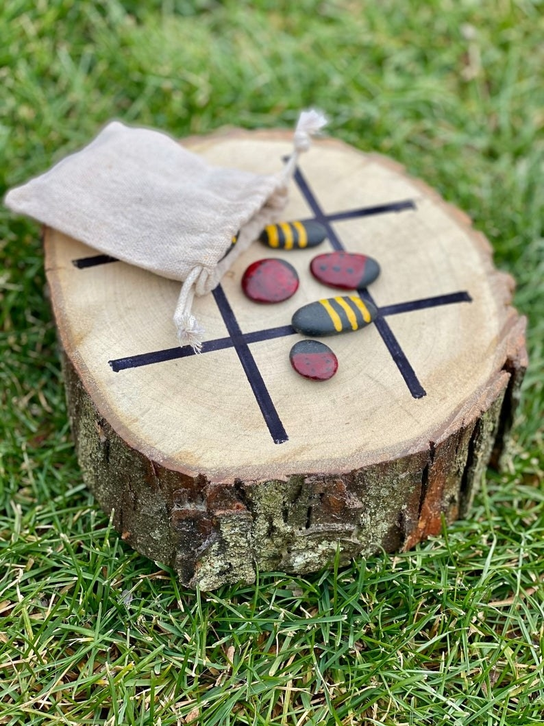 tree stump with painted rocks as a tic tac toe board