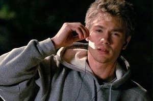 a teenage boy wearing a hoodie puts a headphone into his ear