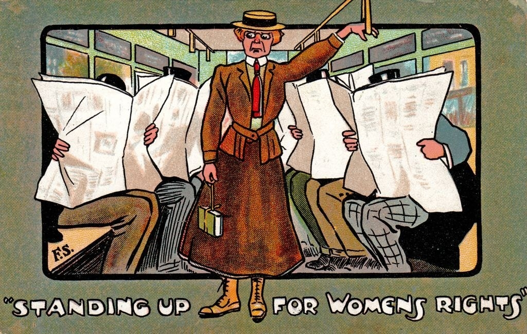 """""""Standing up for womens rights"""" written beneath a woman standing on the bus while man sit and read newspapers, ignoring her"""