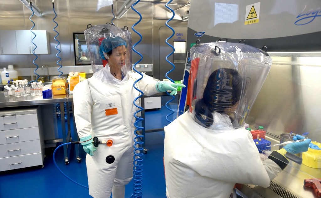Two people wear full-body protective gear inside a lab