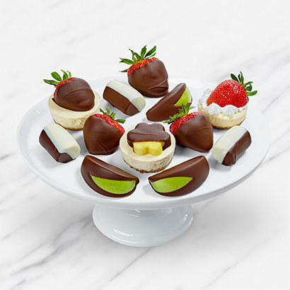a white platter with small round cheesecakes and various chocolate-dipped fruits