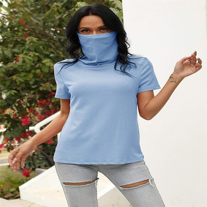 A model wearing the T-shirt in blue with the mask up