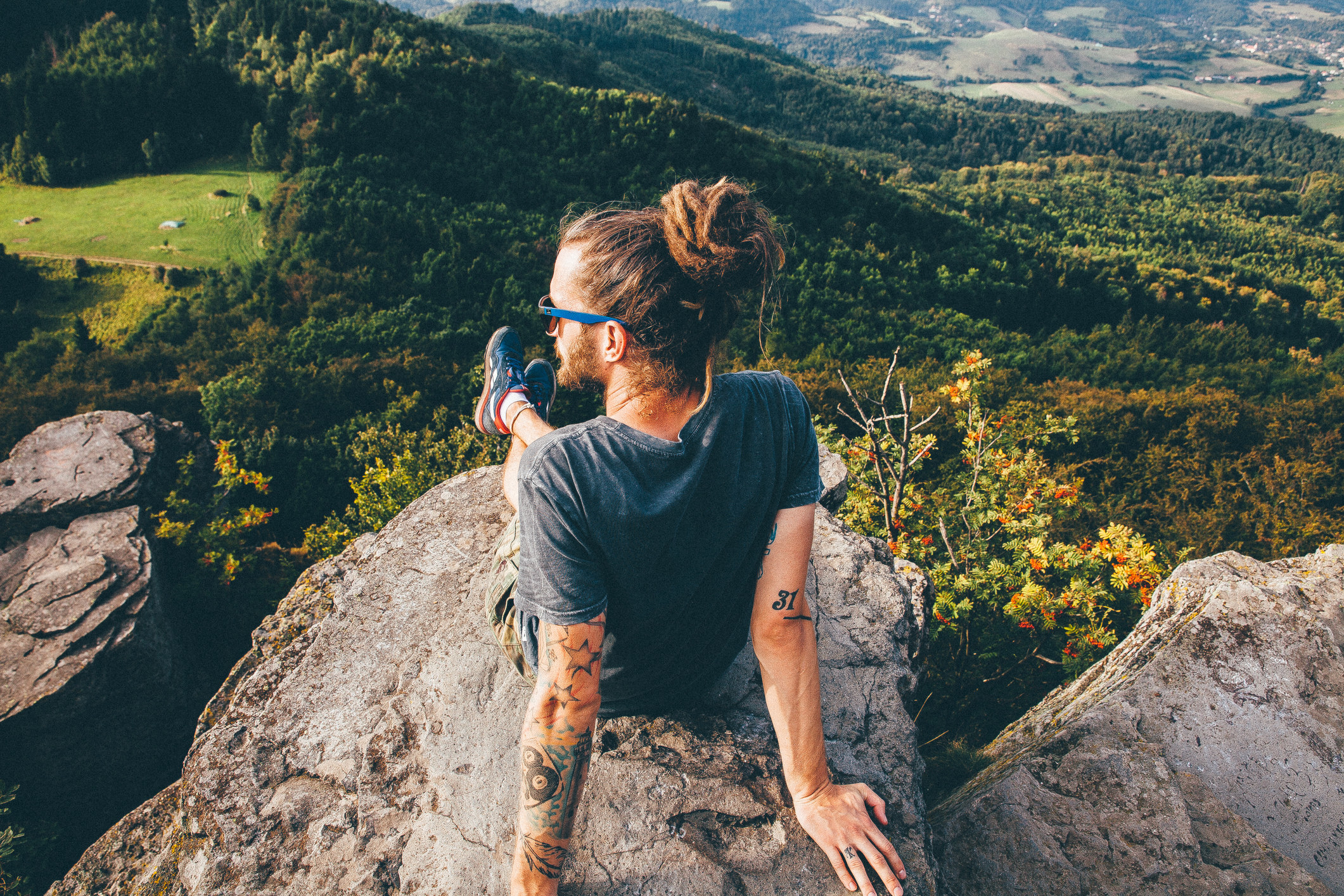 a man with long hair looking out at a nature view