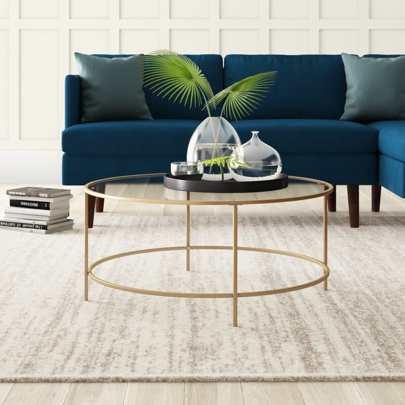 A circular gold framed table with a glass top in a living room