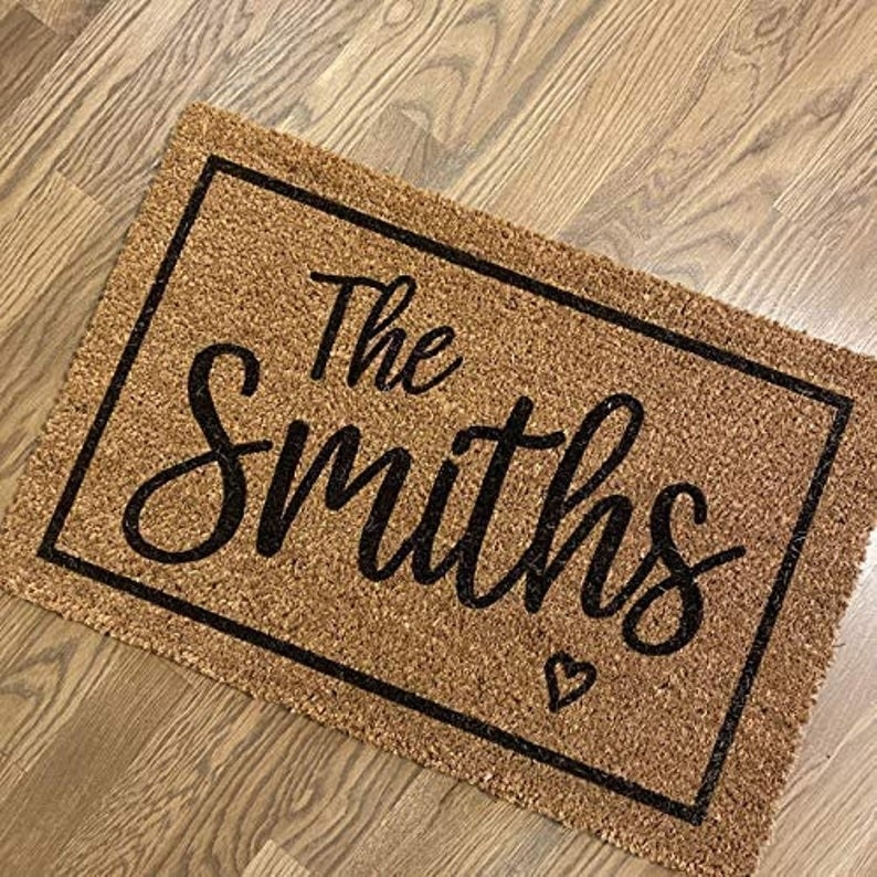 "a brown door mat with a black border and ""the smiths"" written in script with a small black heart under it"