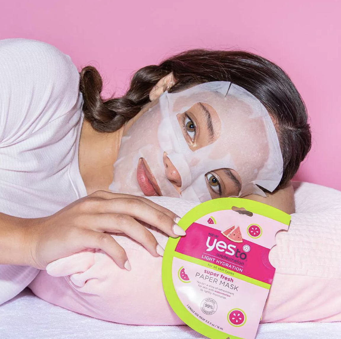 a model wearing a sheet mask and holding the pink and green packaging