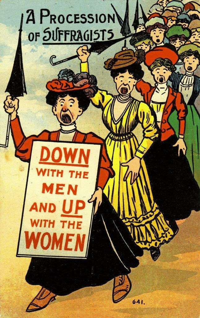"""Women marching and holding a sign that says, """"Down with the men and up with the women"""""""