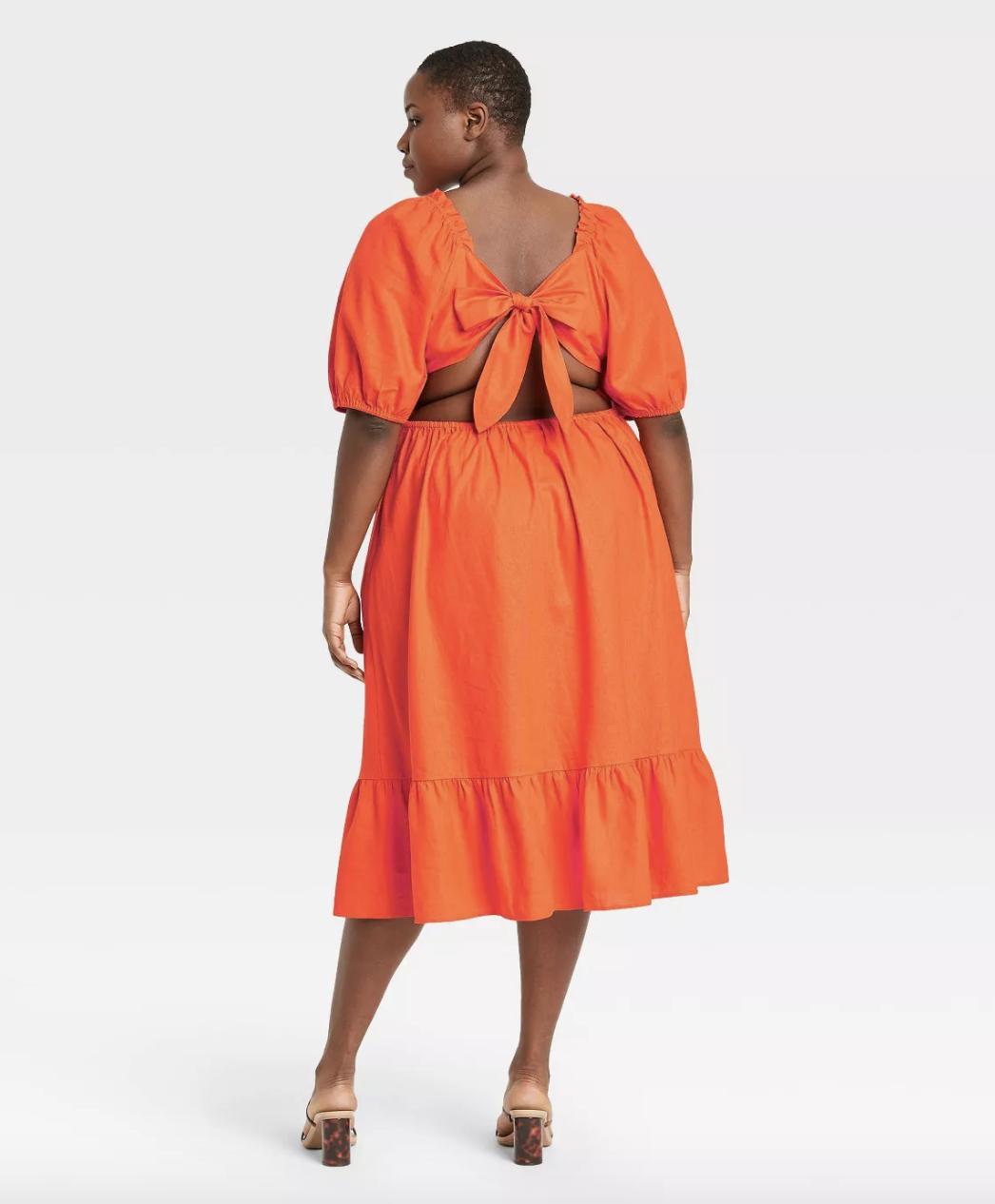 model wearing the orange open back dress