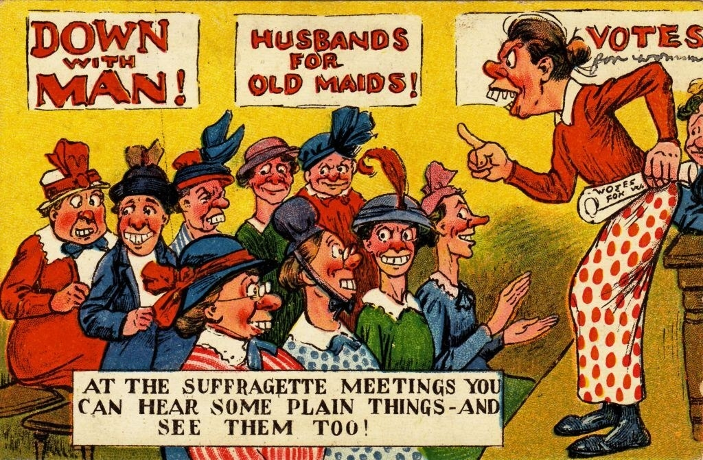 """""""At the Suffragette meetings you can hear some plain things, and see them, too"""" written underneath women at a meeting, with """"Down with man,"""" """"Husbands for old maids,"""" and """"Votes,"""" written on posters behind them"""