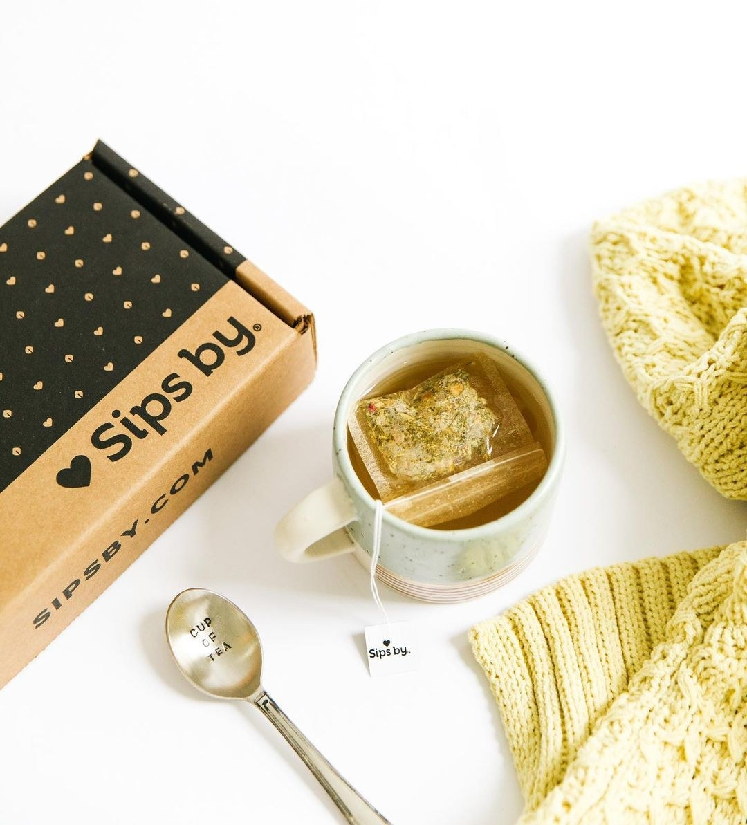 Sips By box styled next to a cup of tea
